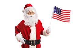 Santa Claus que sostiene una bandera americana foto de archivo