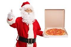 Santa Claus que sostiene una caja de la pizza y que hace un pulgar encima de la muestra imágenes de archivo libres de regalías