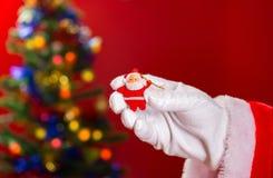 Santa Claus que sostiene una muñeca a mano con la parte posterior adornada del árbol de navidad encendido Fotografía de archivo