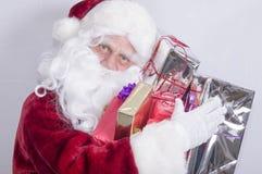 Santa Claus que sostiene una pila grande de presentes Foto de archivo