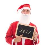 Santa Claus que sostiene una pizarra con la fecha 24 12 , aislado en wh Imágenes de archivo libres de regalías