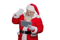 Santa Claus que usa la tableta del ordenador foto de archivo