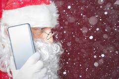 Santa Claus que usa um telefone celular no tempo do Natal Fotografia de Stock Royalty Free