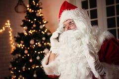 Santa Claus que usa um telefone, sentando-se em uma sala acolhedor foto de stock
