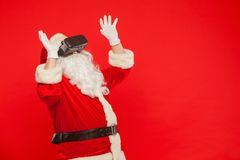 Santa Claus que veste óculos de proteção da realidade virtual, em um fundo vermelho fotografia de stock