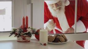 Santa Claus quiere probar la leche y las galletas y mirar a través de un vidrio almacen de metraje de vídeo