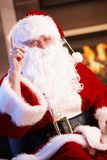 Santa Claus raising finger. Santa Claus sitting at fireplace, raising finger, looking at camera Stock Photos