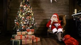 Santa Claus Read Book perto da árvore X-mas vídeos de arquivo