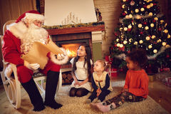 Santa Claus read children`s whishes from long paper Stock Image