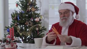 Santa Claus read wish letters sitting at table near Christmas tree. Kind looking Santa Claus in red costume near bright decorated fir tree and fireplace reads stock footage