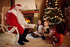 Santa Claus reading fairy tale with children. Santa Claus reading fairy tale with little children Royalty Free Stock Images