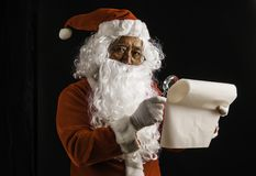 Santa Claus reading gift`s list for children studio shot on black background for family, giving, season, Christmas, holiday, new. Year, travel, Christian and royalty free stock photos
