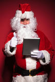 Santa claus is reading about good news on his tablet pad Royalty Free Stock Image