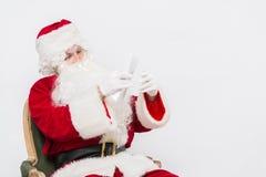 Santa Claus Reading Letter aisló sobre el baclground blanco Fotografía de archivo