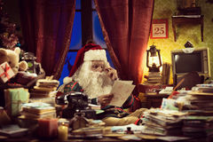 Santa Claus reading a letter Royalty Free Stock Images