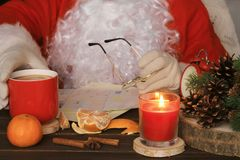 Santa Claus reading letter, drinking tea and eating tangerines. royalty free stock photography