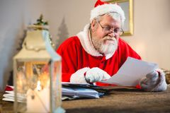 Santa Claus reading a letter. At home Royalty Free Stock Photos