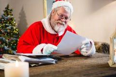 Santa Claus reading a letter. At home Stock Photos