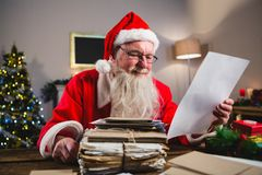 Santa Claus reading a letter. At home Stock Image