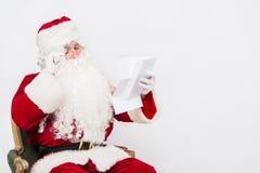 Santa Claus Reading Letter a isolé au-dessus du baclground blanc Photos libres de droits
