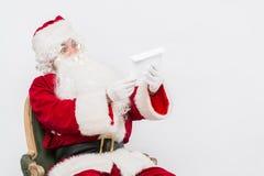 Santa Claus Reading Letter isolerade över vit baclground Arkivfoto