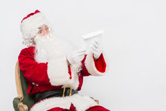 Santa Claus Reading Letter lokalisierte über weißem baclground stockfoto