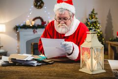 Santa Claus reading a letter. At home stock images