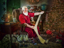Santa Claus reading list. Santa Claus seated in living room checking list next to tree Stock Image