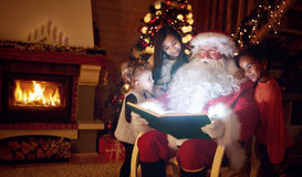 Santa Claus reading magic book with children Stock Photos