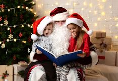 Santa Claus reading magic book to happy little cute children boy and girl kids near Christmas tree Stock Photos