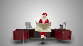 Santa Claus reading a map in his modern Christmas Office, against white, stock footage stock video footage