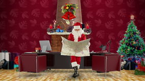 Santa Claus reading a map in his modern Christmas Office, stock footage stock footage