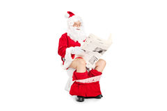 Santa Claus reading a newspaper seated on toilet Royalty Free Stock Photo