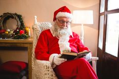 Santa claus reading novel in living room Stock Photography