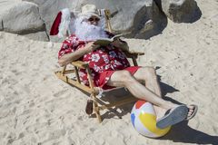 Santa Claus reading novel on sunny beach Royalty Free Stock Images