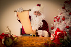 Santa Claus reading scroll Royalty Free Stock Image