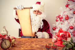Santa Claus reading scroll Stock Images