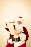 Santa Claus reading scroll Stock Image