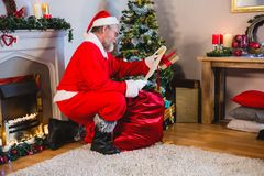 Santa Claus reading scroll in living room stock photo