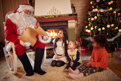 Santa Claus reading wish list with children. Santa Claus reading wish list with little children Royalty Free Stock Images