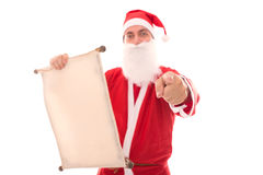 Santa Claus reading in a wish list scroll and pointing to the be Stock Image
