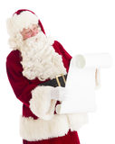 Santa Claus Reading Wish List. While standing isolated against white background Royalty Free Stock Photography