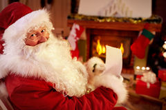 Santa Claus reading wish list in warm home. Claus enjoy in warm home near the fireplace and reading wish list Royalty Free Stock Photo
