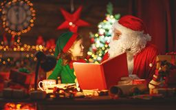 Santa claus reads book to little elf by Christmas tree. Santa claus reads book to little elf by fireplace and Christmas tree stock photography