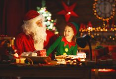 Santa claus reads letter to little elf by Christmas tree. Santa claus reads letter to little elf by fireplace and Christmas tree Royalty Free Stock Photography