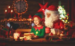 Santa claus reads letter to little elf by Christmas tree. Santa claus reads letter to little elf by fireplace and Christmas tree Royalty Free Stock Images