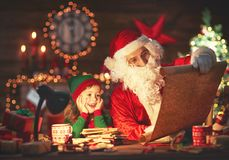 Santa claus reads list of good children to little elf by Christm Royalty Free Stock Image
