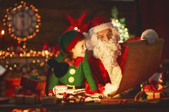Santa claus reads list of good children to little elf by Christm Stock Image