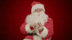 Santa claus reads and sends text messages from his cell phone on red background with snow. Professional shot on BMCC RAW with high dynamic range. You can use royalty free stock photo