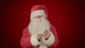 Santa claus reads and sends text messages from his cell phone on red background with snow. Professional shot on BMCC RAW with high dynamic range. You can use royalty free stock photography